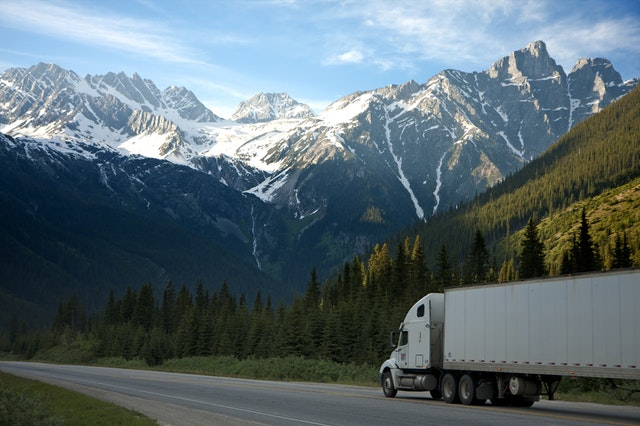 truck on road in front of mountains